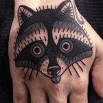 Татуировка с енотом на кисти руки