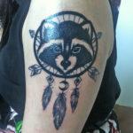 Татуировка с енотом на плече