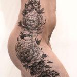 Черно белая татуировка пионов на бедре переходящая на бок