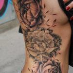Черно белая татуировка пионов на боку