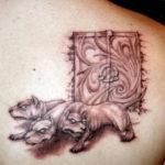 Объемная татуировка с цербером на лопатке
