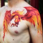 Тату птицы феникс у парня на плече и переходит на грудь