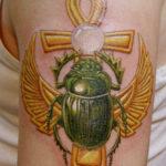 Татуировка жука скарабея седящего на золотом ангхе