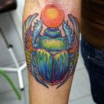 Тату жука скарабея держащего солнце