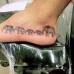 Тат слонов держащихся друг за друга за хвосты