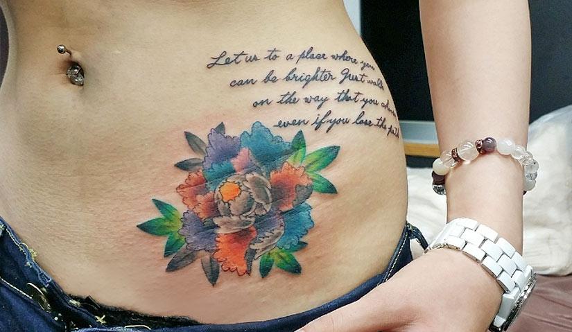 Татуировка с разноцветным пионом и надписью