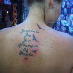 Татуировка с чайками на спине и надписи