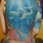 Тату на всю спину с дельфинами и разноцветными рыбками