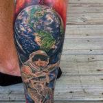 Цветная тату космонавта на фоне земли