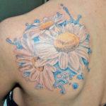 Татуировка с ромашками и водой на лопатке