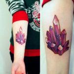 Татуха с гроздью кристаллов рубина на руке
