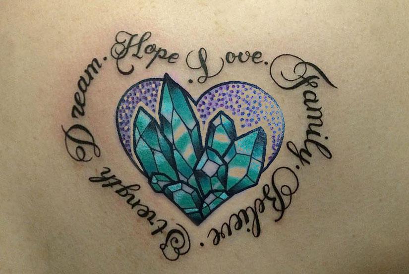 Татуировка с кристаллом и надписью в виде сердечка