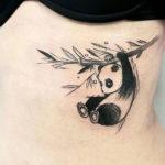 Панда висит на ветке бамбука
