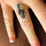 Скрипичный ключ на указательном пальце, женская тату
