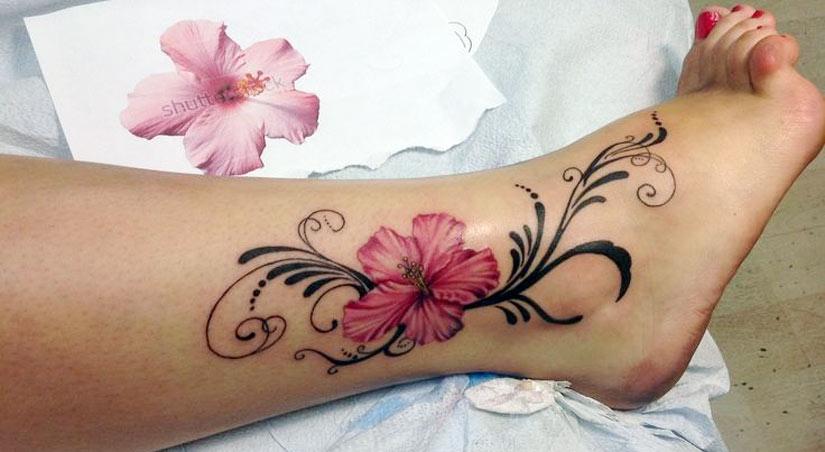 Красивая тату цветка с орнаментом спускающаяся от икры до ступни