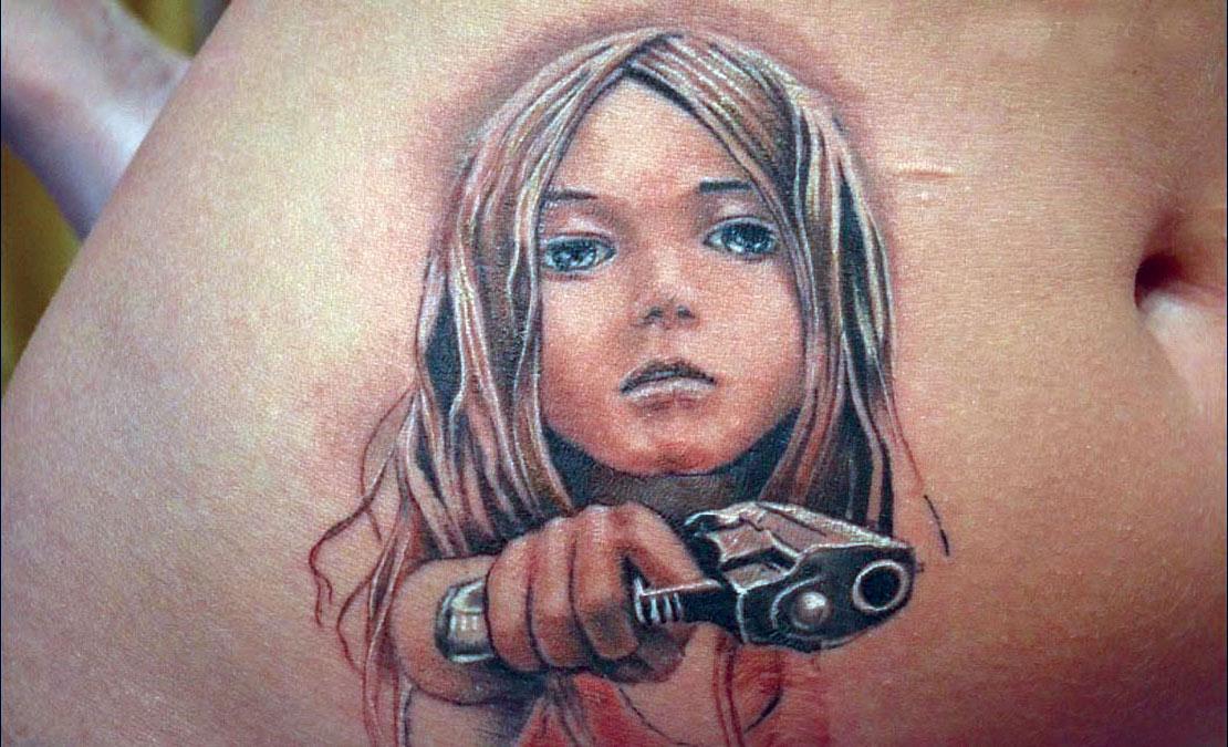 Современная татуировка на животе девочка с пистолетом