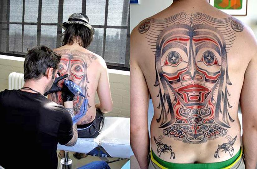 Тату мастер делает татуировку клиенту