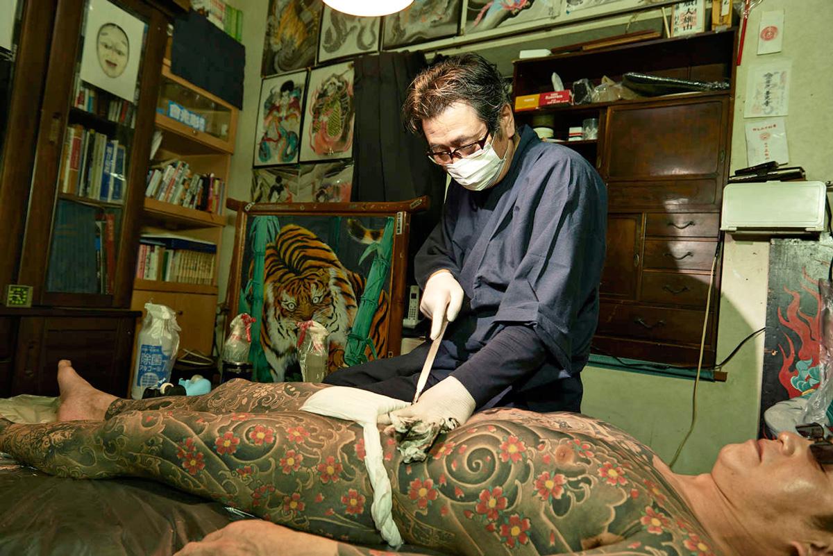 Мастер японских татуировок делает тату традиционным способом