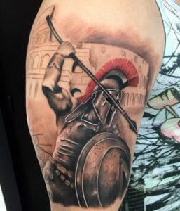 Хорошая татуировка гладиатора с копьем на фоне арены