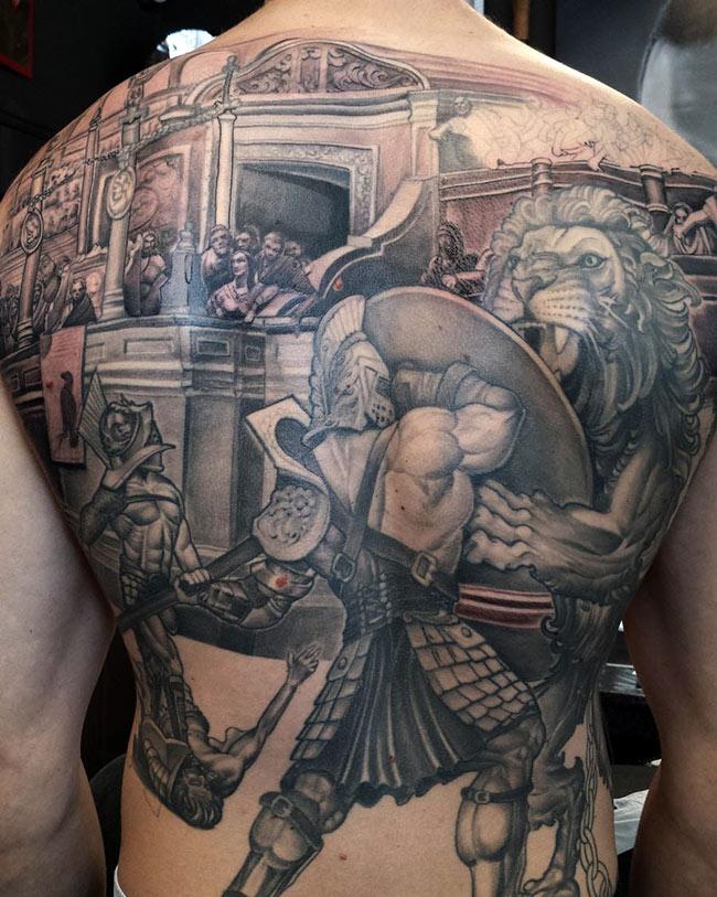 Многодетальная большая татуировка гладиатора на спине в схватке со львом