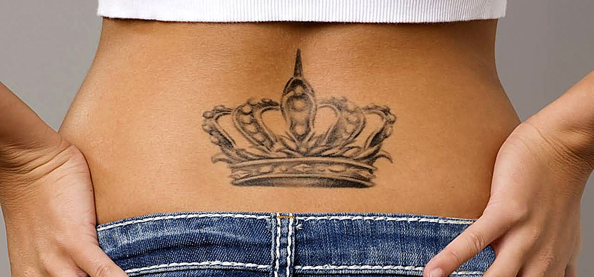 Татуировка короны у девушки на пояснице