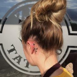Татуировка полевого цветка за ухом