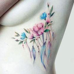 Композиция тату с полевыми цветами и перьями