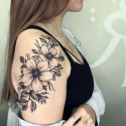 Черно-белая тату полевых цветов на плече девушки