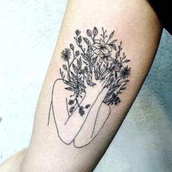Абстрактно-графическая тату полевых цветов в виде девушки