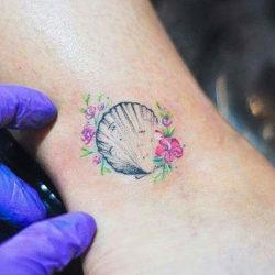 Ракушка гребешка с полевыми цветами на руке