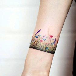 Редкое тату на руке в виде браслета вокруг запястья и полевых цветков