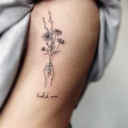 Тату полевых цветов в руке с надписью