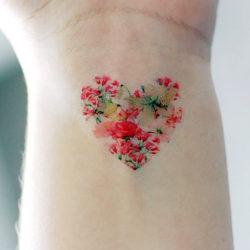 Миниатюрная тату в виде сердца из полевых цветов