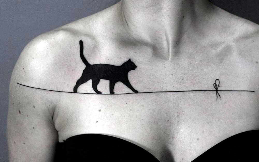Татуировка у девушки на груди, кошка идущая по веревке